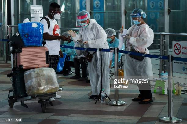 Passengers arriving on international flights are received by workers wearing personal protective equipment to be protected from COVID-19 before...