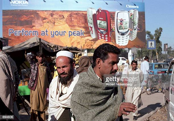 Passengers at a bus stop wait for transport below a Nokia cell phone billboard December 21 2001 at the Fateh Jang Intersection near Islamabad Pakistan