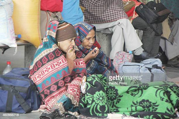 Passengers at a railway station wear warm clothes to protect themselves from cold winds on a cold foggy and chilly morning in Allahabad on Tuesday...