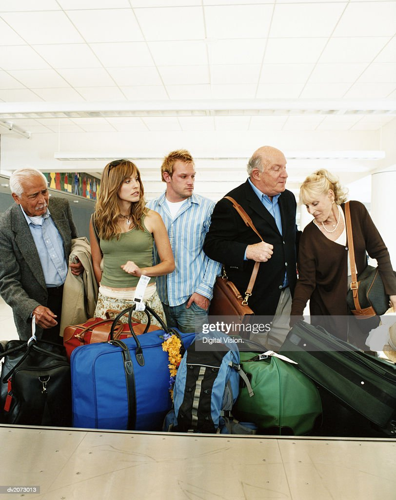 Passengers at an Airport Baggage Collection Searching For Their Luggage : Stock Photo