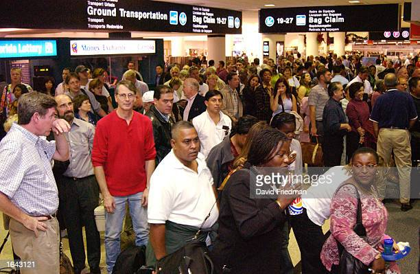 Passengers at Concourse D of Miami International Airport wait for security screening to reopen after a security breach occurred at the airport...