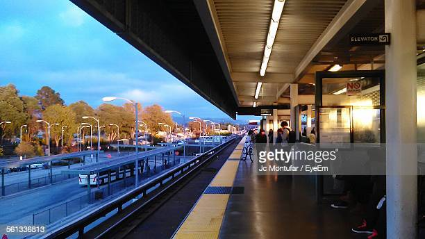 passengers at railroad station platform - san leandro stock photos and pictures