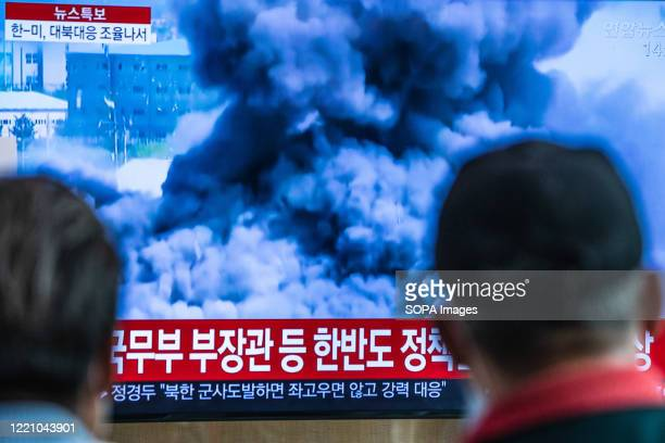 Passengers at Seoul station watch TV news showing a video that North Korea blows up liaison office used for talks with South Korea. North Korea...