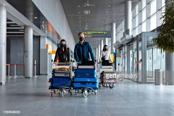 passengers at the airport with luggage, wearing n95 face masks - airport stock pictures, royalty-free photos & images