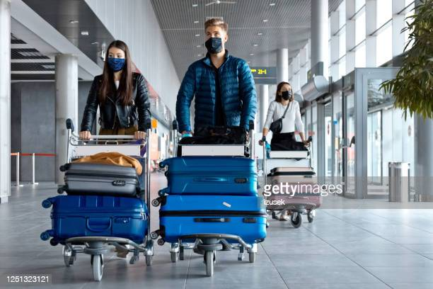 passengers at the airport with luggage, wearing n95 face masks - aeroplane stock pictures, royalty-free photos & images