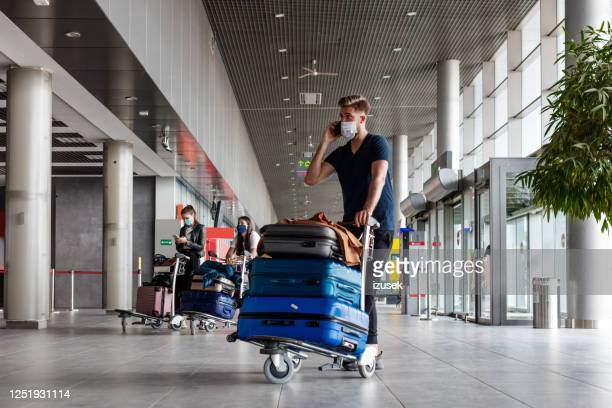 passengers at the airport with luggage, wearing n95 face masks - carrying stock pictures, royalty-free photos & images