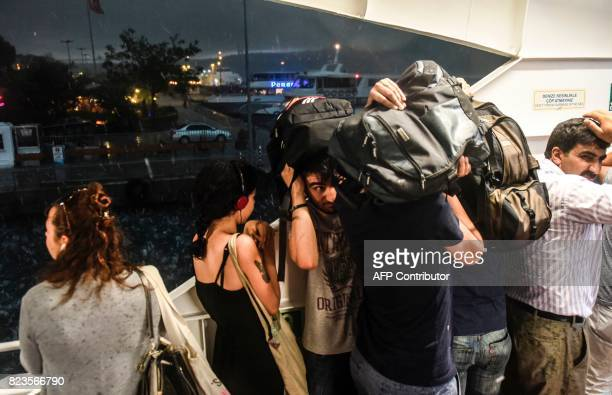Passengers attempt to shelter from a heavy downpour of rain and hail as they travel on a ferry across The Bosphorus at Istanbul on July 27 2017 / AFP...