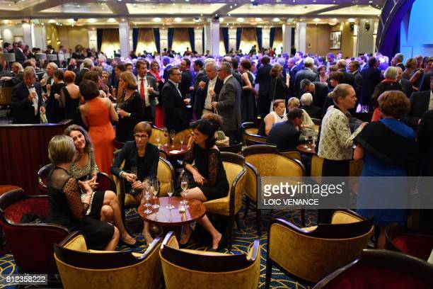 Passengers attend a captain's cocktail party on the Cunard cruise liner RMS Queen Mary 2 sailing in the Atlantic ocean during the Bridge 2017 a...