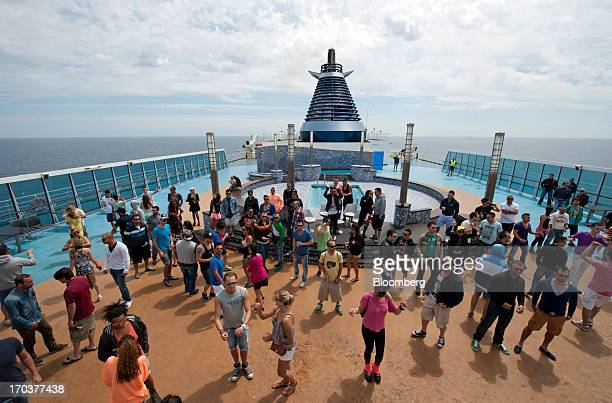 Passengers attend a party on the deck of the 'Cruise Barcelona' passenger ship operated by Grimaldi Compagnia Di Navigazione SpA as it travels to...