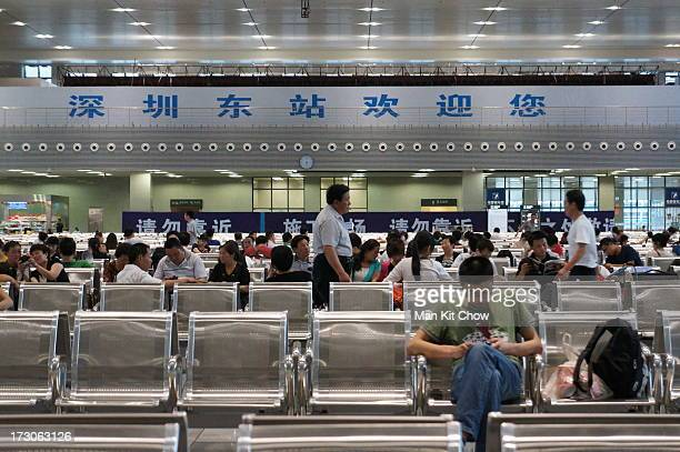 """Passengers awaiting in the waiting hall at Shenzhen East Railway Station. The simplified Chinese characters in the background means """"Shenzhen East..."""