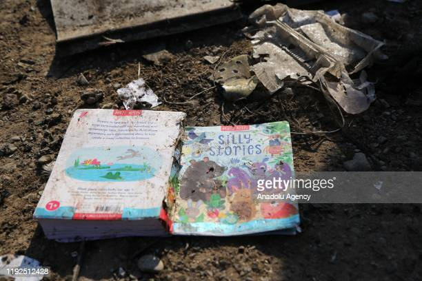 Passengers' belongings are seen as search and rescue works are conducted at site after a Boeing 737 plane belonging to a Ukrainian airline crashed...