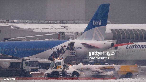 Passengers board a BMI aircraft as a snow plough passes at Heathrow Airport on December 20 2010 in London England Severe weather has caused major...