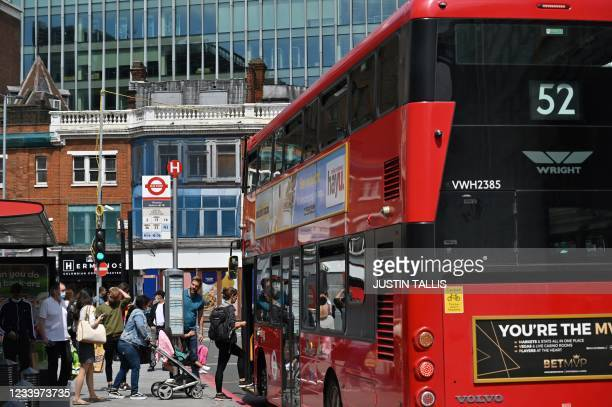 Passengers board a bus at a bus stop in central London on July 14, 2021. - London Mayor Sadiq Khan called for use of face coverings to remain...