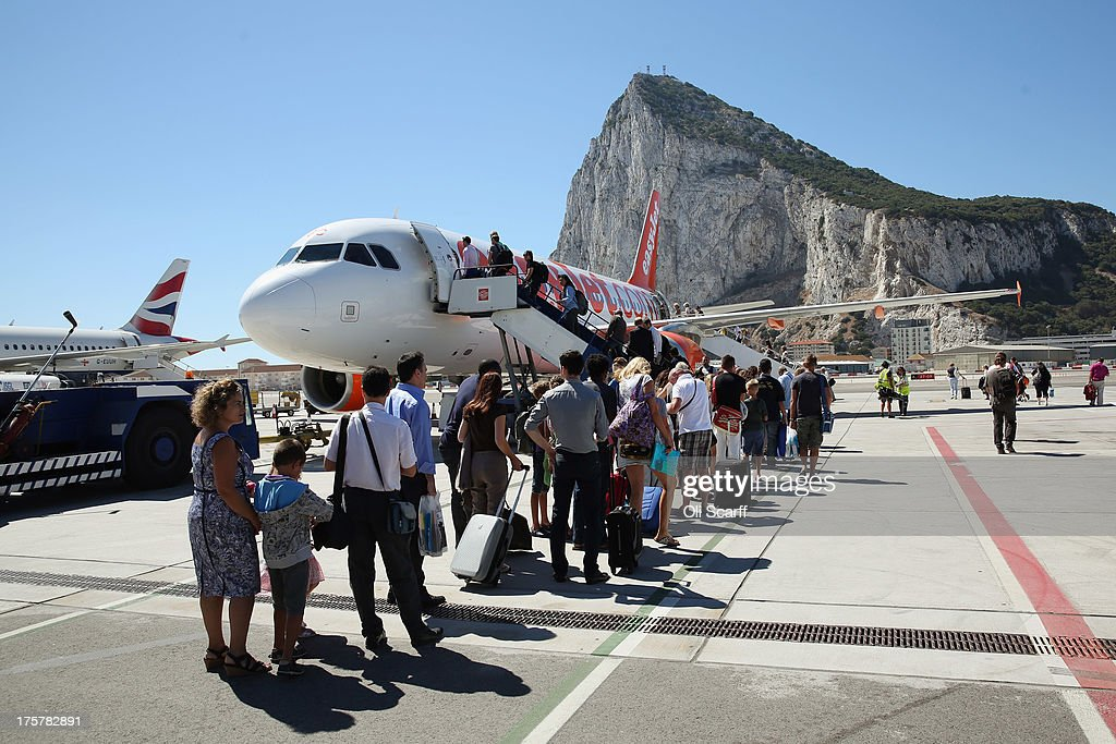 Passengers board a flight at Gibraltar International Airport on August 8, 2013 in Gibraltar. David Cameron has spoken with his Spanish counterpart, Mariano Rajoy, and Mr Rajoy has offered to 'reduce measures' at the Gibraltar border. Tensions between the British and Spanish governments have been raised on issues surrounding the sovereignty of Gibraltar. An increase in Spanish border crossing checks between the Rock and mainland Spain, leading to lengthy queues, is widely considered to be a retaliatory move for the construction of an artificial reef in British waters, which it is claimed has had a negative impact on Spanish fishing vessels in the area.