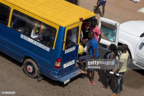 Passengers board a public minibus known locally as 'tocatoca' in Bissau GuineaBissau on Monday Feb 12 2018 The International Monetary Fund said an...