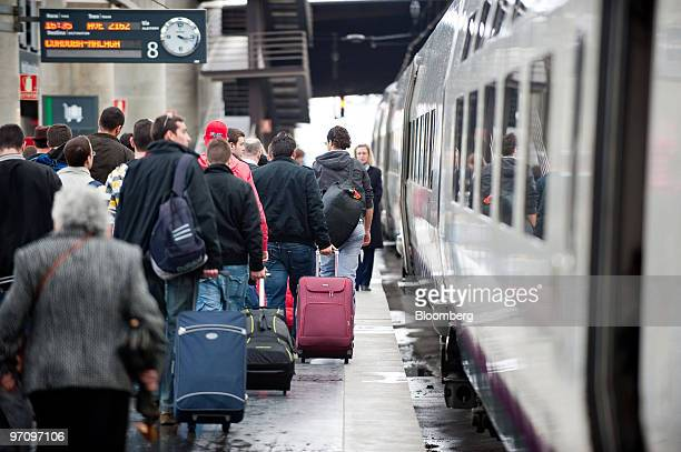 Passengers board a Renfe operated AVE highspeed train at Atocha station in Madrid Spain on Thursday Feb 25 2010 Spanish stateowned rail company Renfe...