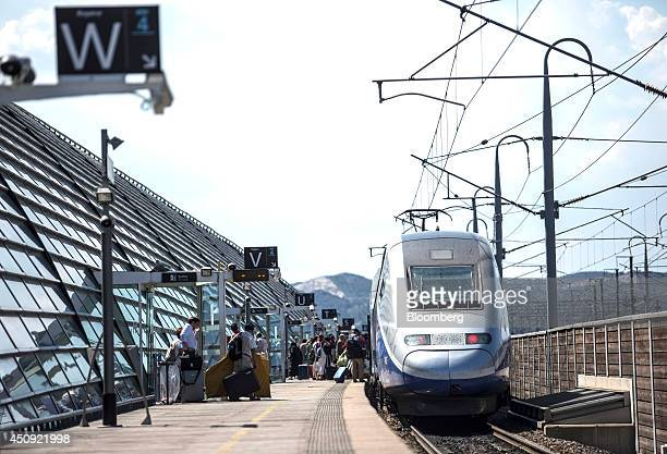 Passengers board a TGV duplex highspeed train operated by Societe Nationale des Chemins de Fer and manufactured by Alstom SA as it stands in the...