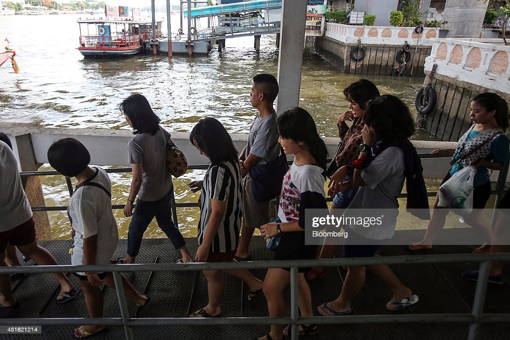 Passengers board a tourist boat on the Chao Phraya river at the Saphan Taksin pier in Bangkok, Thailand, on Saturday, June 28, 2014. Through a dozen coups, a tsunami, financial upheaval, floods and riots, Bangkok keeps bouncing back. With each crisis, tourism numbers slump, stocks crash and investment dips, only to return stronger than before. Photographer: Dario Pignatelli/Bloomberg via Getty Images