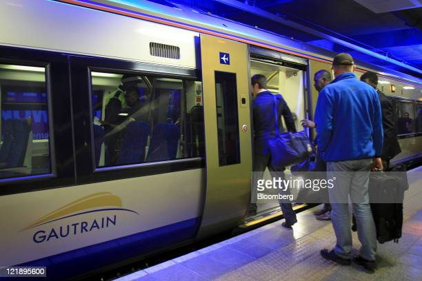 Passengers board a train at Gautrain's Sandton mass transit rail station in Johannesburg South Africa on Monday Aug 22 2011 South Africa expanded its...