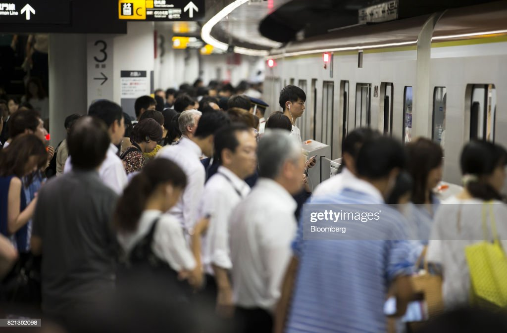 Passengers board a train at Shibuya Station in Tokyo, Japan, on Tuesday, July 18, 2017. July 24 marks the first dry run of a 'Telework Day' encouraging people to work from home as the city gears up to host the 2020 Summer Olympics. Authorities are seeking ways to make room for 920,000 spectatorsexpected to visit Tokyo each day during the games. Photographer: Tomohiro Ohsumi/Bloomberg via Getty Images