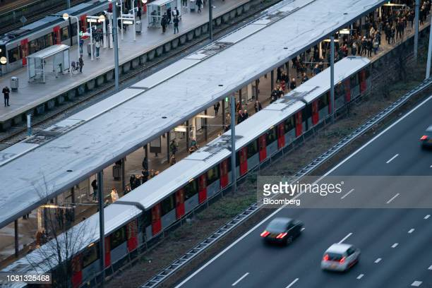 Passengers board a train at the metro station next to a highway in the Zuidas financial district in Amsterdam Netherlands on Friday Jan 11 2019 A...