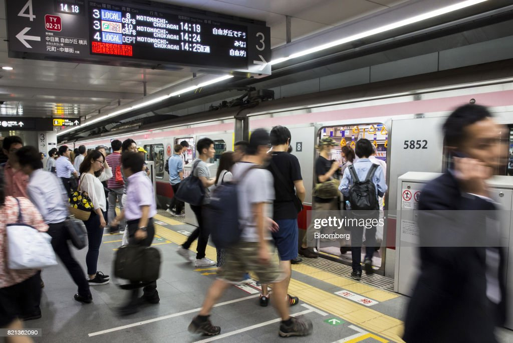 Passengers board a train on the Toyoko line operated by Tokyu Corp. at Shibuya Station in Tokyo, Japan, on Tuesday, July 18, 2017. July 24 marks the first dry run of a 'Telework Day' encouraging people to work from home as the city gears up to host the 2020 Summer Olympics. Authorities are seeking ways to make room for 920,000 spectatorsexpected to visit Tokyo each day during the games. Photographer: Tomohiro Ohsumi/Bloomberg via Getty Images