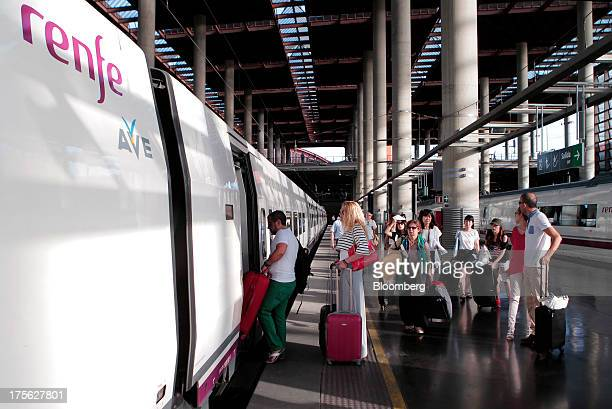 Passengers board an Alta Velocidad Espanola highspeed train operated by Renfe Operadora SC as it sits at a platform at Atocha train station in Madrid...