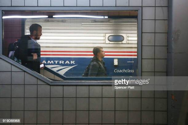 Passengers board an Amtrak train at New York's Pennsylvania Station on February 16 2018 in New York City Amtrak gave a media tour on Friday to show...