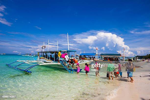 Passengers board an outrigger boat at Boracay, Philippines