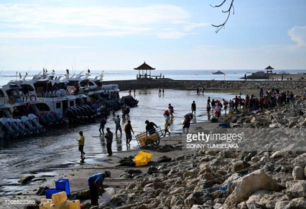 Passengers board fast boats to cross from Sanur to Nusa Penida island, on Indonesia resort island of Bali on March 7, 2020.