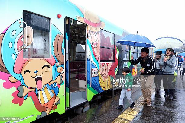 Passengers board the sightseeing train featuring the characters of the popular manga 'One Piece' at Takamori Station on November 21 2016 in Takamori...