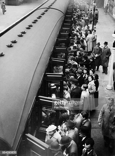 Passengers boarding a train at a busy platform Ilford Essex 1st May 1937