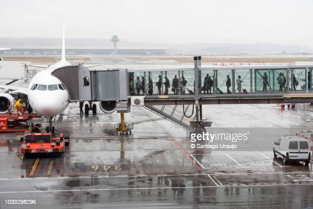 passengers boarding an airplane through a boarding bridge - boarding stock pictures, royalty-free photos & images