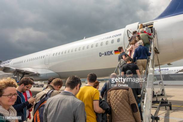 passengers boarding in a lufthansa airplane in frankfurt airport, germany - frankfurt international airport stock pictures, royalty-free photos & images