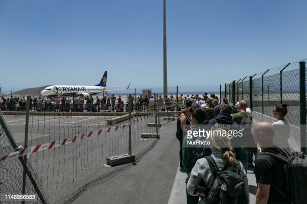 Passengers boarding Ryanair low cost airline aircraft for a flight to central Europe on Tenerife South Airport Reina Sofia Airport TFS GCTS or...