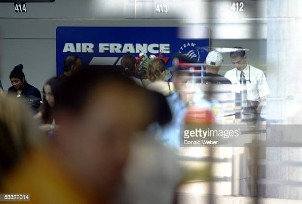 Passengers can be seen checking in for an Air France flight to Paris looking through a window at Pearson International Airport August 3 2005 in...