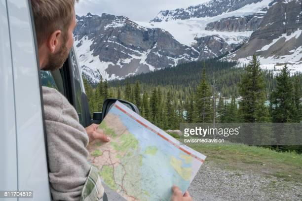passagierszijde auto kijken routekaart in berglandschap - canadian rockies stockfoto's en -beelden