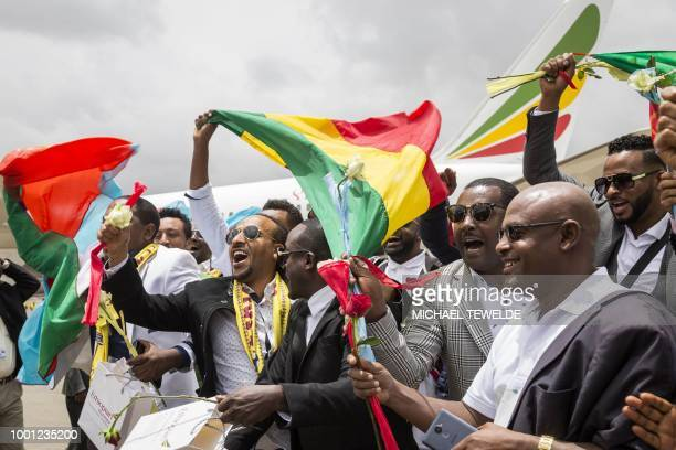 Passengers carrying Ethiopian and Eritrean flags celebrate on the tarmac upon their arrival at the Asmara International airport on July 18 2018...