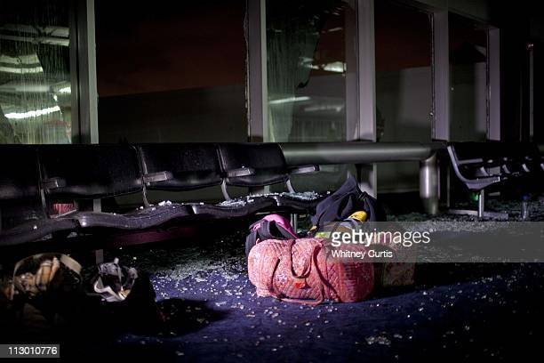 Passengers' carryon bags sit below a shattered window on Concourse C at LambertSt Louis International Airport's Terminal One after an apparent...