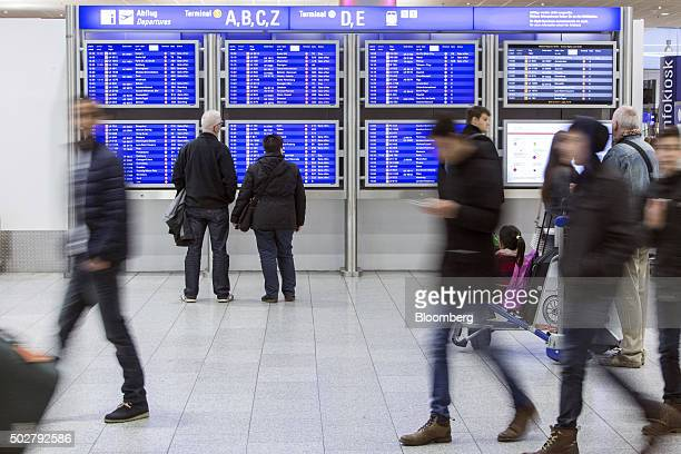 Passengers check an electronic departures board inside Terminal 1 at Frankfurt Airport operated by Fraport AG in Frankfurt Germany on Monday Dec 28...