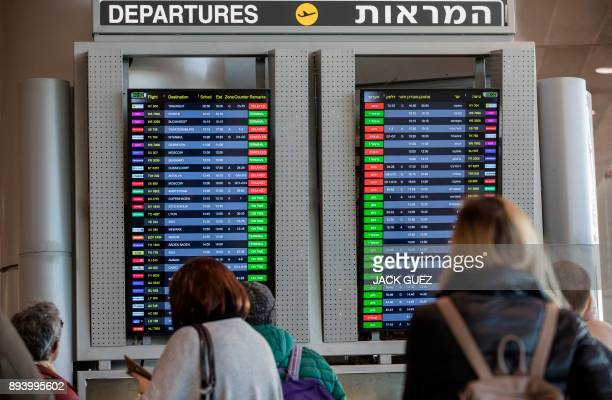 Passengers check an information board indicating delayed or cancelled flights during a strike at the Ben Gurion Airport near the Israeli city of Tel...