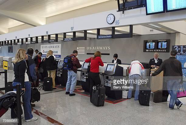Passengers check in at the US Airways counter at Atlanta Hartsfield Jackson International Airport November 15 2006 in Atlanta Georgia US Airways is...