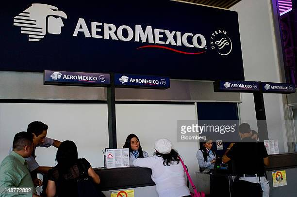 Passengers check in for flights at a Grupo Aeromexico SAB ticket counter at the Comalapa International Airport in Comalapa El Salvador on Tuesday...