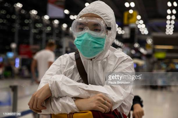 Passengers check in wearing protective gear to protect themselves against the Coronavirus at Suvarnabhumi International airport on March 25 2020 in...