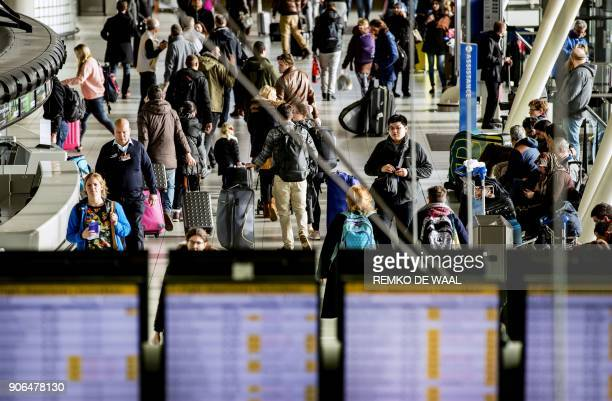 Passengers check plane departures timetables at Amsterdam's Schiphol airport on January 18 2018 after all flights were briefly cancelled as winds...
