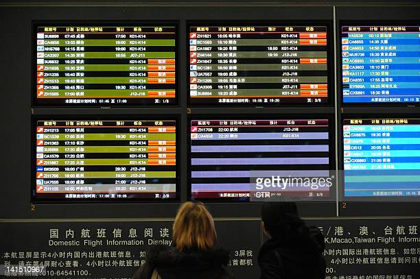 Passengers check the board for announcements while waiting for their flights as almost 250 flights were cancelled including some 15 international...