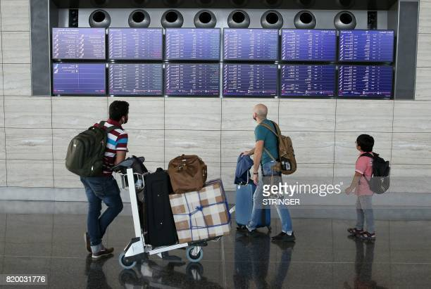 Passengers check the departures board at the Hamad International Airport in Doha on July 20 2017 / AFP PHOTO / STRINGER