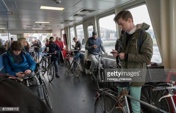 Passengers check their cellphones onboard a ferry sailing to Central Station from NDSM on April 21 2017 in Amsterdam Netherlands GVB ferries...