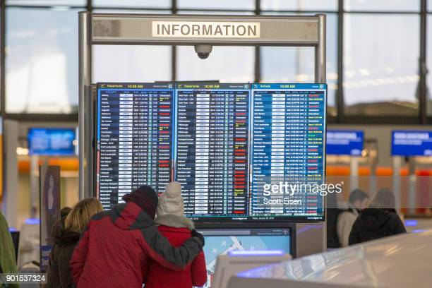 Passengers check TV displays for cancellations at Logan International Airport following a 'bomb cyclone' the previous day on January 5 2018 in Boston...