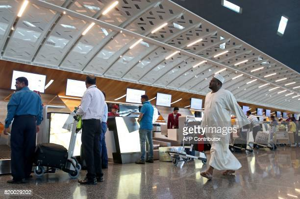 Passengers checkin for a Qatar Airways flight at the Hamad International Airport in Doha on July 20 2017 / AFP PHOTO / STRINGER